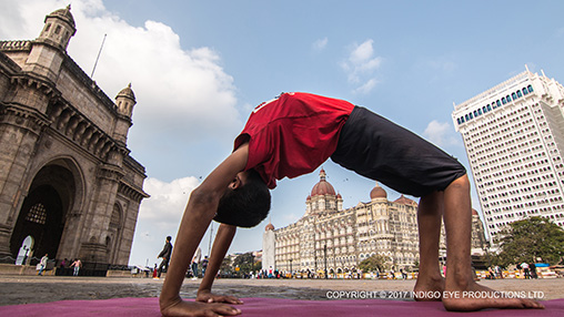 A young boy performs yoga