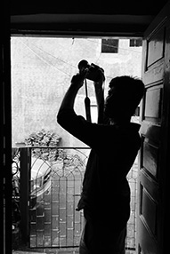 Black and white shot of a young Indian man with a camera