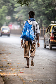 Young Indian man walking in the road with no shoes on