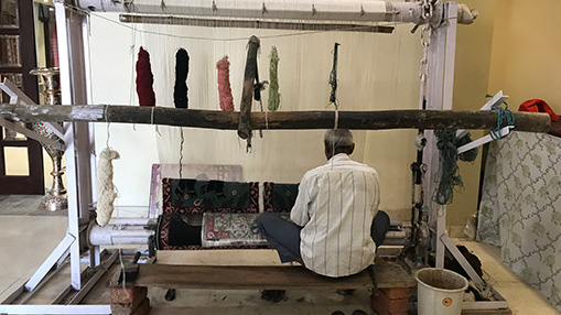 An Indian man is sitting on a bench with wool hanging down from a large wooden beam