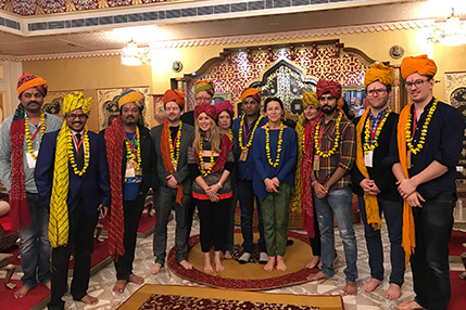 Thirteen men and women all posing for a photo with turban headwear on